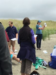 Rachel Stendahl, Chehalis Basin Education Consortium, and Aleks Storik, explain COASST protocol on the beach